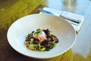 Slow cooked egg with a salad of duck hearts, bacon and hazelnuts